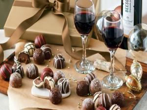 Bombones y dos copas de vino tinto en una mesa