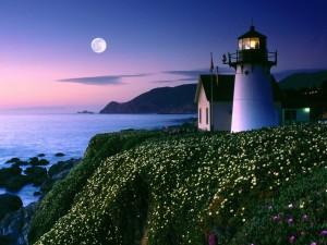 Luna llena brillando junto al faro