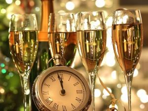 Copas con champán y un reloj marcando la llegada del Nuevo Año