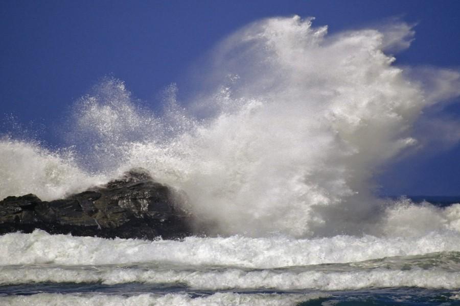 Gran ola chocando contra la roca