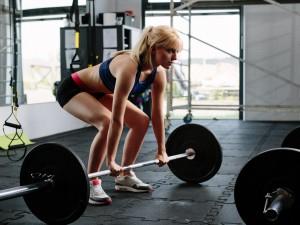 Mujer rubia entrenando con una barra