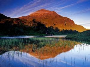 Montaña marrón junto al lago