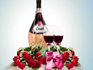 Romántico arreglo floral junto a una botella de vino Chianti y dos copas
