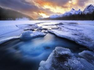 Salida del sol sobre un río helado y montañas nevadas