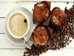 Taza de cappuccino junto a unos muffins de chocolate y granos de café