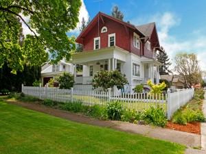 Hermosa casa de dos pisos con jardines y cerca de madera