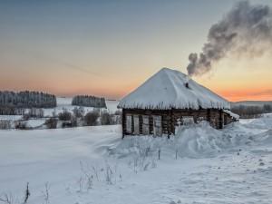 Casa de madera con chimenea en una mañana invernal