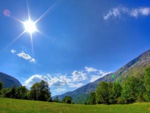 Radiante sol alumbrando el valle y las montañas
