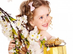 Niña de pelo rizado con su regalo y flores