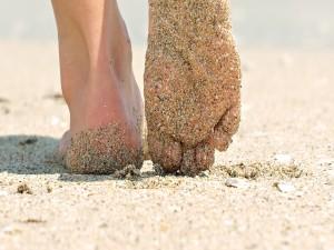 Dos pies que caminan en la arena bajo el sol de verano