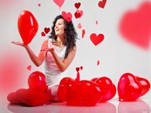 Mujer feliz con globos rojos en forma de corazón