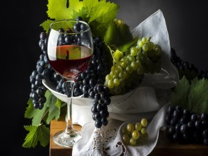 Uvas blancas y negras junto a una copa de vino tinto