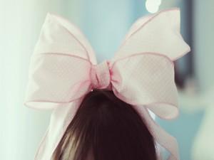 Gran lazo rosa en el cabello de una niña