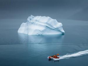 Personas en un bote contemplando un iceberg en el mar Ártico