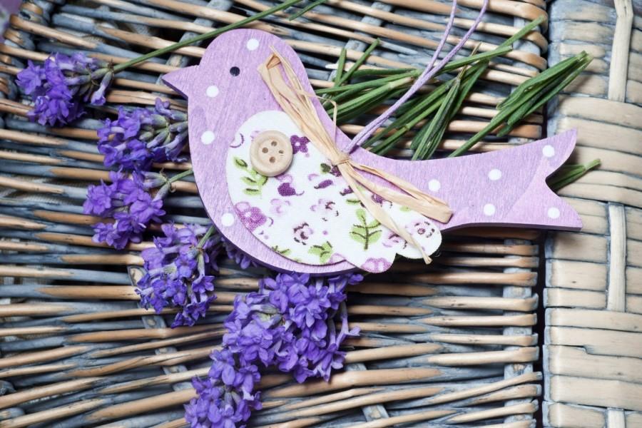 Bonito adorno decorativo con forma de pájaro sobre unas flores