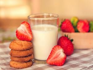 Galletas y fresas junto a un vaso de leche