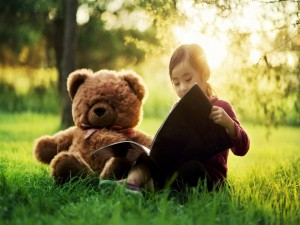 Niña contándole un cuento a su oso de peluche