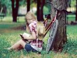 Chica leyendo junto a una bicicleta