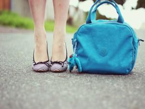 Las piernas de una chica junto a un bolso azul