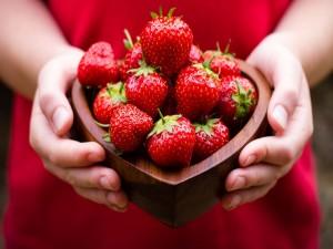 Sosteniendo un cuenco con fresas