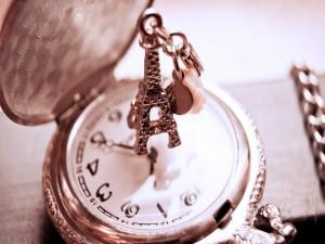 Pequeño llavero de la Torre Eiffel sobre un reloj