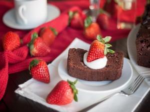 Un trozo de pastel de chocolate con una fresa