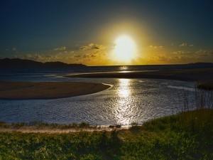 Los rayos del sol bañan las aguas en el horizonte