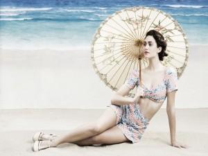 Emmy Rossum sentada en una playa