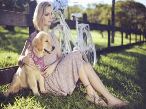 Chica sentada en la hierba junto a un perro