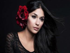 Una guapa morena con una rosa en el cabello