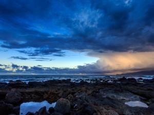 Nubes sobre la playa rocosa
