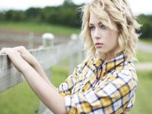 Chica junto a una valla de madera