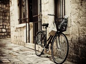 Bicicleta apoyada en una pared de piedra