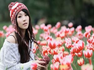 Chica sentada entre tulipanes
