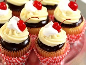 Unos cupcakes de chocolate con frosting y guindas