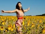 Mujer feliz caminando por un campo de girasoles