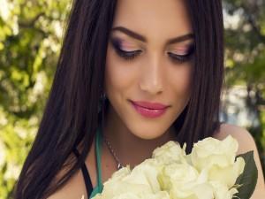 Una dulce morena sonriente con un ramo de rosas blancas