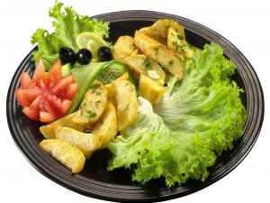 Un plato con patatas fritas y ensalda