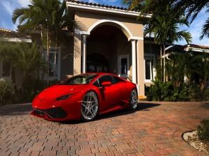 Ferrari rojo frente a una hermosa casa