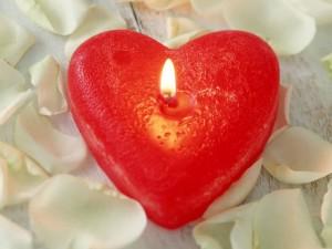 Pétalos de rosa y una vela en forma de corazón