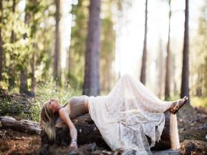 Mujer tumbada sobre un tronco del bosque