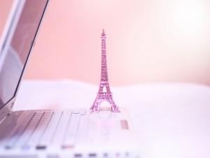 Pequeña Torre Eiffel de color rosa sobre un ordenador portátil