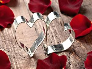 Dos corazones de metal entre pétalos de rosa