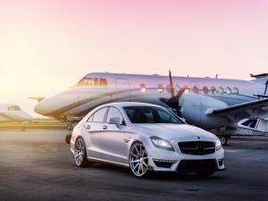 Mercedes Benz CLS junto a un jet privado