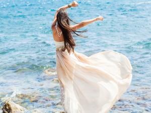 Mujer con vestido blanco frente al mar