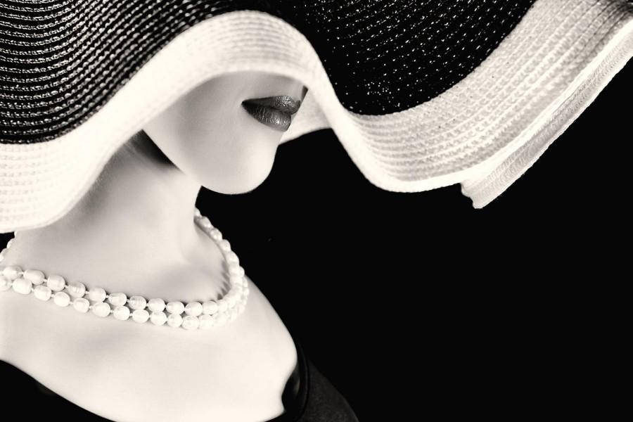 Elegante dama con un sombrero y un collar