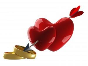 Anillos de boda y dos corazones con una flecha