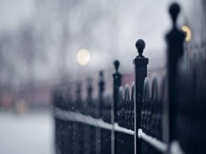 Copos de nieve cayendo junto a una valla negra