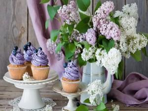 Exquisitos cupcakes junto a un jarrón con lilas