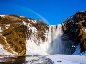 Arcoíris sobre una cascada invernal